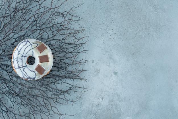 大理石の背景の乾燥した枝の束に置かれたドーナツ。高品質の写真
