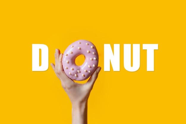 Текст пончика с розовым пончиком в женской руке вместо буквы «o» на оранжевом.