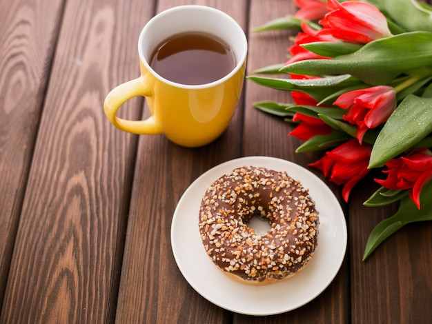 Donut on white plate with red tulips and cup of tea on a brown wooden surface. breakfast in summer time, top view, copy space