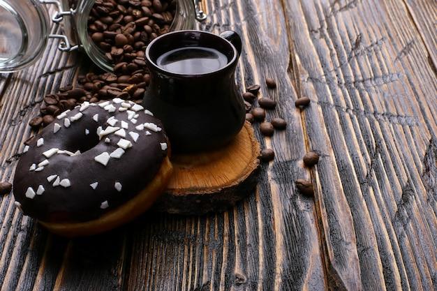 黒いアイシングとチョコレートパウダーと本物の濃いコーヒーの入ったドーナツ。コーヒー豆と注がれた穀物の缶。