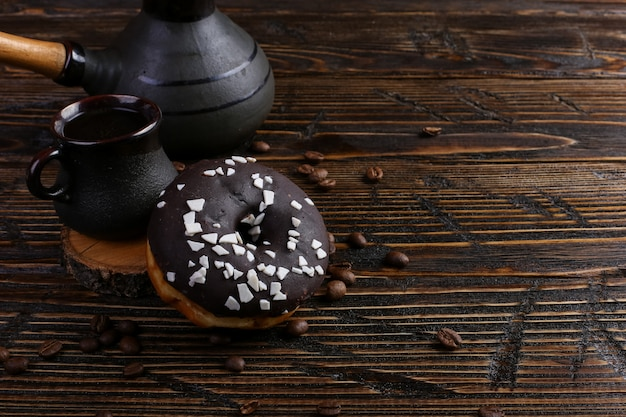 Donut with black icing and chocolate powder and an authentic cup of strong coffee. a can of coffee beans and poured grains.