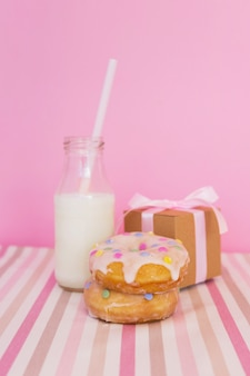 Donut with candle, present and milk