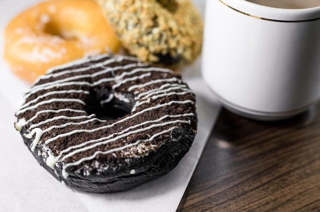 Donut with coffee on a wooden table.