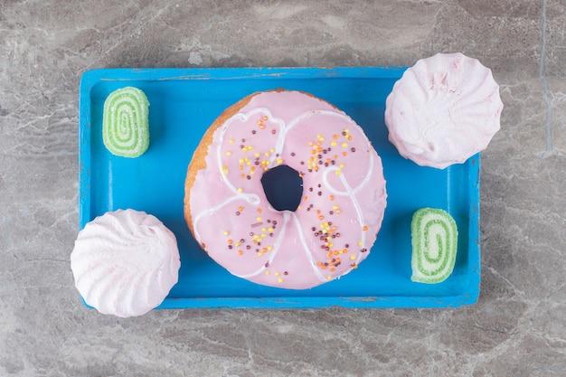 Una ciambella con caramelle gommose e biscotti su un piatto da portata su superficie di marmo