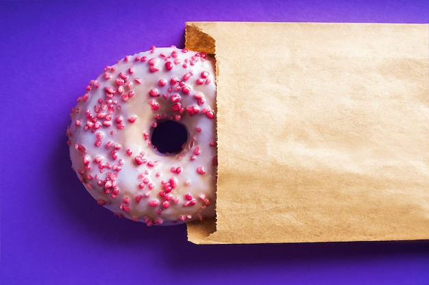 Donut with purple and pink powder close-up on blue table. food delivery concept, donut in kraft wrapping paper and copy space.