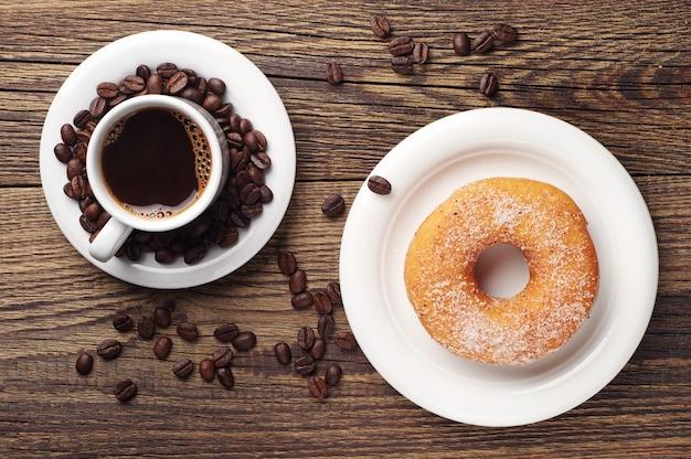 Пончик с сахаром и чашкой кофе