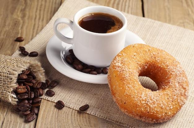 Пончик с сахаром и чашкой горячего кофе