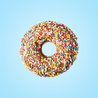 Пончик с украшением сладкого цвета на ярком фоне.