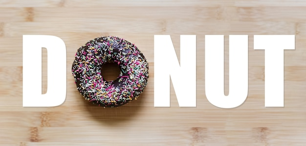 Donut word with chocolate glazed donut instead of 'o' letter, on wooden table.