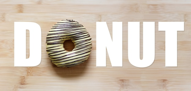 Donut word, with donut instead of 'o' letter, on wooden table.