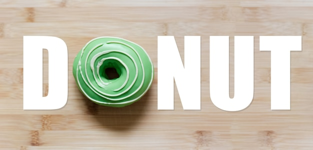 Donut word with green donut instead of 'o' letter, on wooden table.