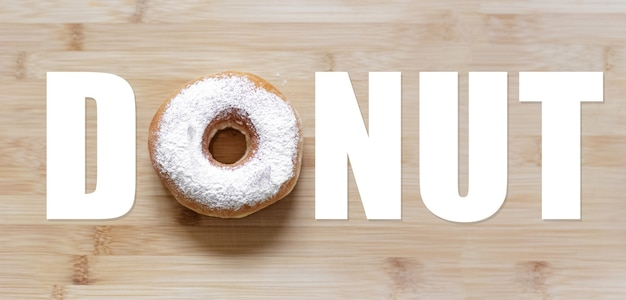 Donut word with white donut instead of 'o' letter, on wooden table.