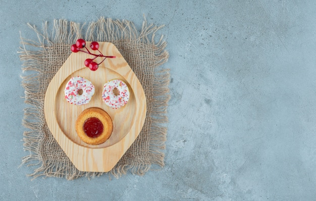 도넛과 대리석 배경에 나무 플래터에 젤리 가득 케이크. 고품질 사진