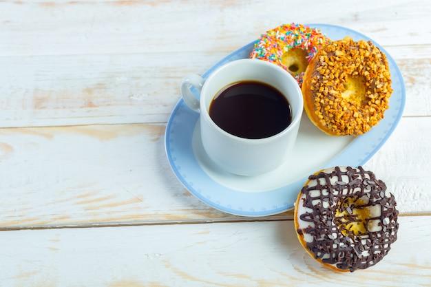 흰색 나무 배경에 도넛과 커피입니다.