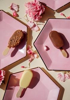 Пончики и мороженое на тарелках с лепестками диантуса на пастельной поверхности