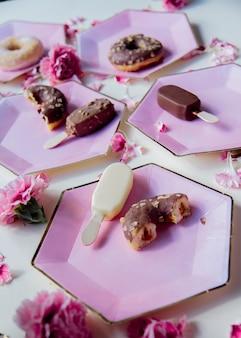 Пончики и мороженое на тарелках с лепестками диантуса
