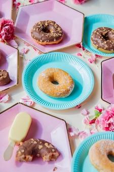 패랭이꽃 꽃잎이 달린 접시에 도넛과 아이스크림