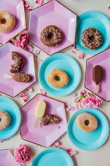 패랭이꽃 꽃잎이 달린 접시에 도넛과 아이스크림 프리미엄 사진