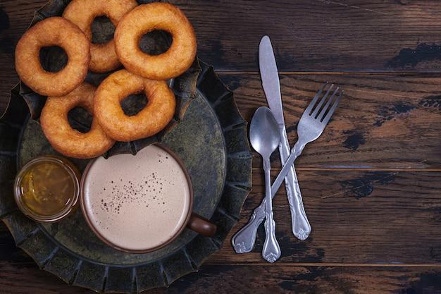 ドーナツと木製のテーブルの上にコーヒーカップとジャム。甘い不健康な朝食