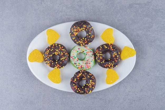 Пончики и мармелады, аккуратно разложенные на блюде на мраморной поверхности.