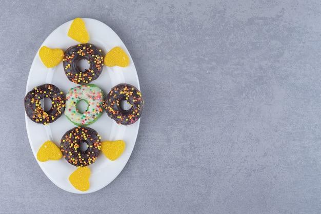대리석 표면의 플래터에 깔끔하게 배열 된 도넛과 마멜 레이드
