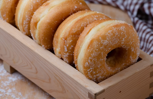 Donuts are arranging in the wooden box