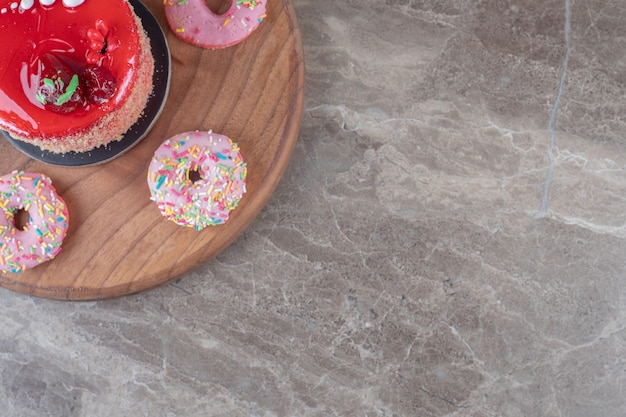 대리석 표면의 보드에 딸기 시럽을 얹은 케이크 주위의 도넛