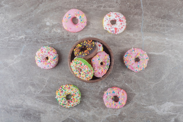 Donuts in and around a small bowl on marble surface