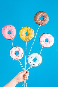 青い背景の上の子供の手の風船としてドーナツ。お誕生日おめでとうパーティー。面白いコンセプト。