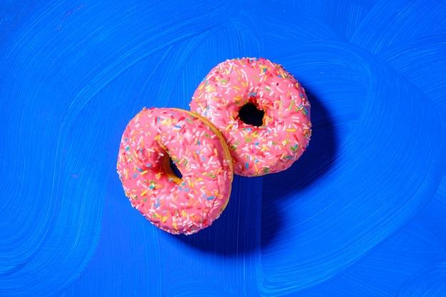 Пончики крупным планом на синем фоне.