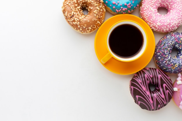 Donuts next to coffee copy space