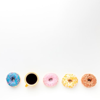 Donuts and coffee on plain background