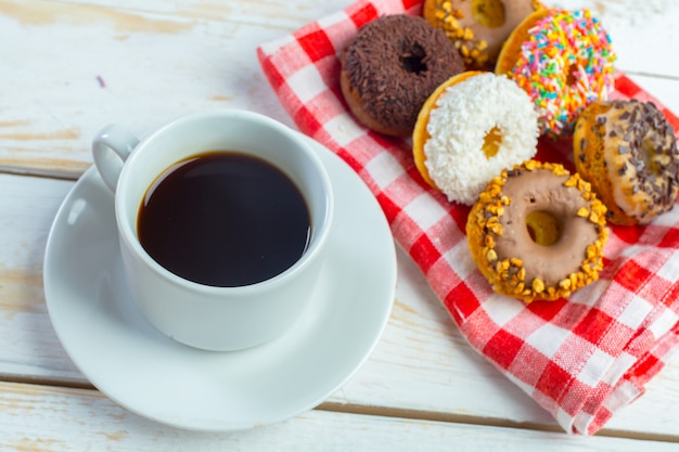 Donuts and coffee on a white wood background.