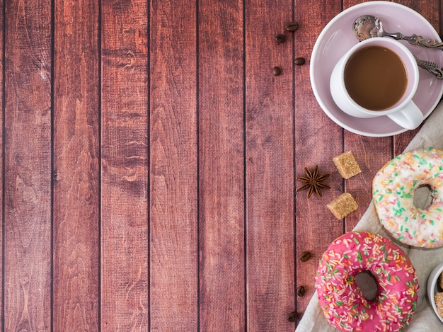 Donuts and coffee on wooden table. top view with copy space.