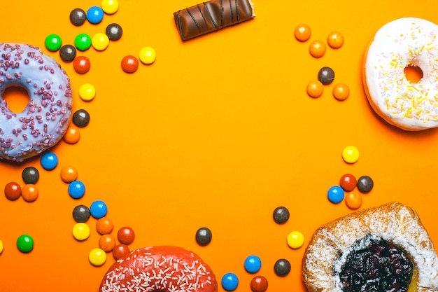 Donuts с покрашенными вишнями замороженности и плюшки с напудренными сахаром .colored помадки шоколада на оранжевом взгляд сверху космоса экземпляра предпосылки.