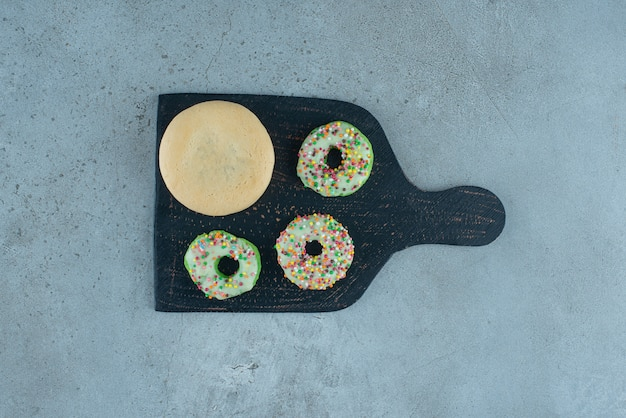 Donuts and a cookie on a black board on marble background. high quality photo