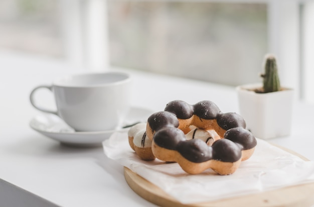 Donuts and cup of coffee on a white wood table