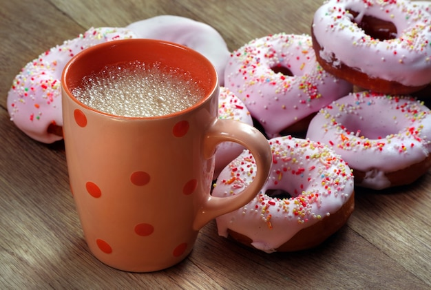 Donuts and cup of drink on wooden background