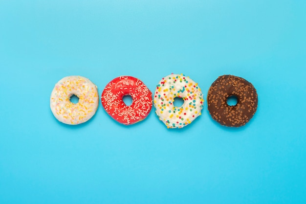Donuts of different types on a blue surface. concept of sweets, bakery,. . flat lay, top view