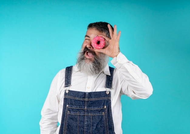 Donuts food baked goods. sweets and cakes. junk food. bearded hipster with blue breastplate with sweet donuts around one eye on a light blue