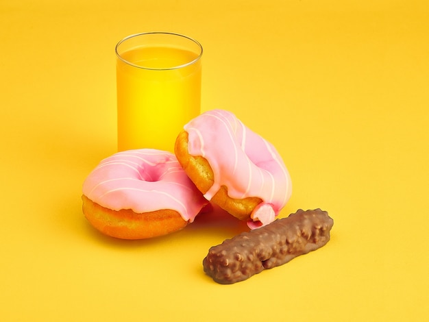 Donuts and fresh orange juice on yellow