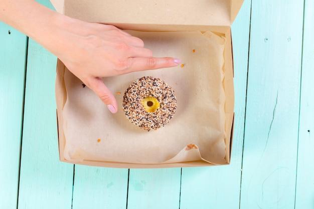 Пончики в коробке на деревянный стол. вид сверху