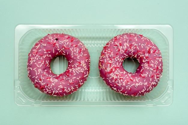 Пончики в пластиковой упаковке. в красной глазури. на синем фоне. сладкий десерт.
