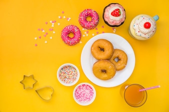 Donuts, juice, cupcakes and pastry cutter on yellow background