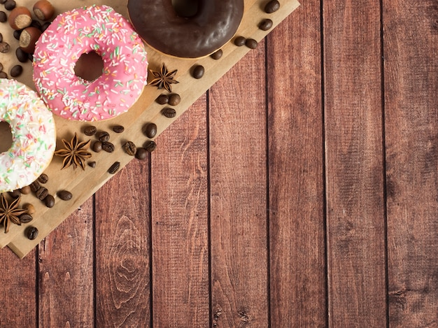 Donuts lie on the paper coffee beans on wooden rustic surface