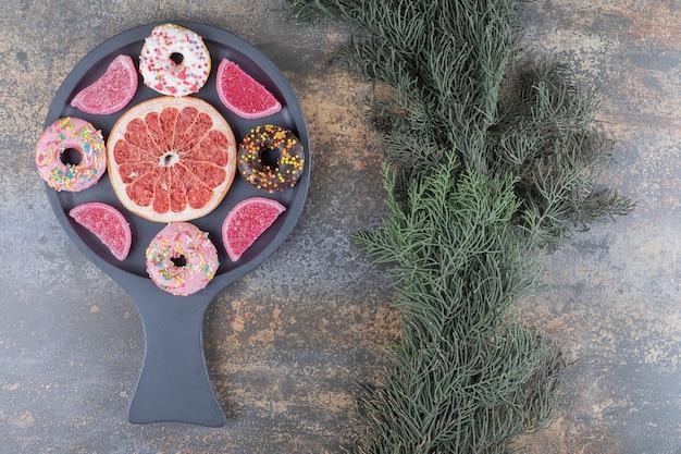 Пончики, мармелад и ломтик грейпфрута, аккуратно разложенные в сервировочном лотке на деревянной поверхности