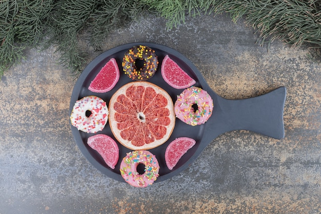 Donuts, marmelades and a grapefruit slice neatly arranged in a serving pan on wooden surface