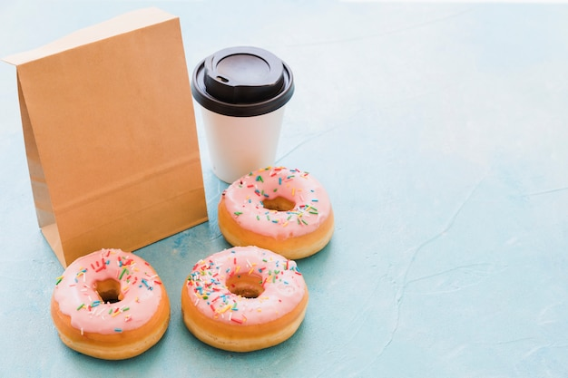 Donuts near package and disposal cup on blue background