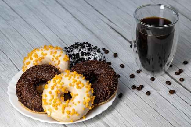 木製のテーブルとコーヒーの白い皿にドーナツ
