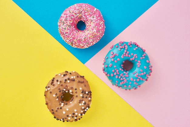 Пончики на пастельных розовый, желтый и синий фон. минимализм креативная пищевая композиция. стиль плоской планировки